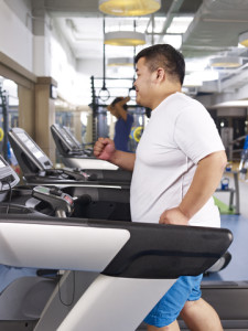 Overweight Man Exercising On Treadmill